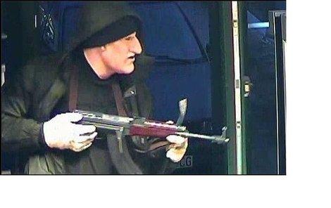 Muž v masce Klause vniká do budovy banky.