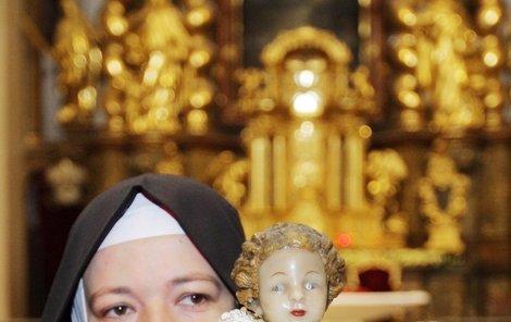 Sestra řádu Karmelitek obléká jezulátko. Jako když si holčičky hrají s panenkami...