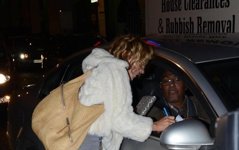Geri Halliwell se naklání k řidiči stříbrného auta.