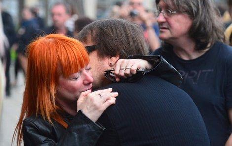 Bára Štěpánová pláče na rameni klávesáka Olympiku Jiřího Valenty. Za nimi stojí Ivan Hlas.