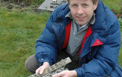 Stanislav Krejný ukazuje zbytky bronzových štítků, které zloději poztráceli. Nové nápisy byly vyrobeny z pryskyřice.
