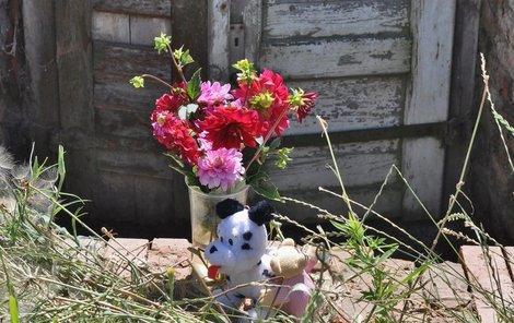 Před sklep, kde našli mrtvolky tří novorozenců, někdo dal květiny a plyšáka.