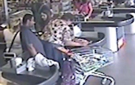 Seniorka v květované haleně platí. Zloděj obhlíží situaci, jeho parťačka mu kryje záda.