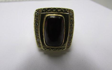 Zlatý šperk se vsazeným rubínem a deseti diamanty.