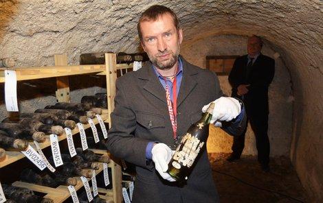 Kastelán Tomáš Wizovský ukazuje jednu lahev.