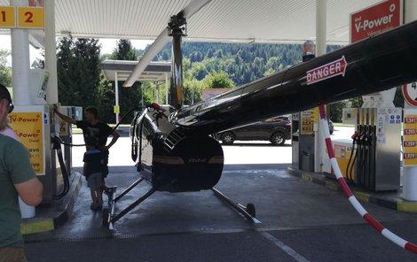 Český pilot přistál u vjezdu na čerpačku a společně s kamarády dotlačil vrtulník přímo ke stojanu.