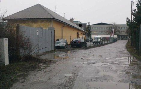 Těšínská, Opava. Příjezdová cesta na parkoviště je plná děr.