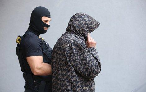 Jan Holman míří k soudu, který mu prodloužil vazbu. Před novináři skrýval tvář.