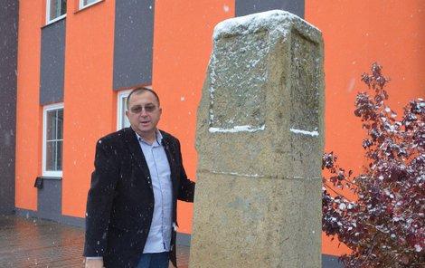Šéf firmy Jaroslav Nožička ukazuje milník stojí poblíž vchodu.