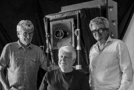 Největší existující polaroid světa na filmy velikosti 20x24 palců, tedy 51x61 cm. Před ním jeho majitel Jan Hnízdo, sedící Manfred Heiting a zcela vpravo Tono Stano.