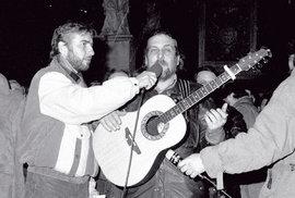 Listopad 1989,  náměstí Svobody, Brno:  zpívá Wabi Daněk,  mikrofon mu drží  Miroslav Donutil.