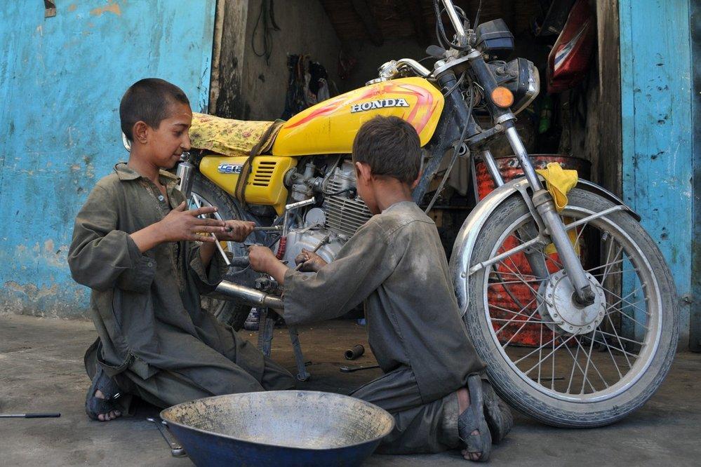 Dva malí kluci dokáží pracovat s motorkou stejně jako dospělí mechanici.