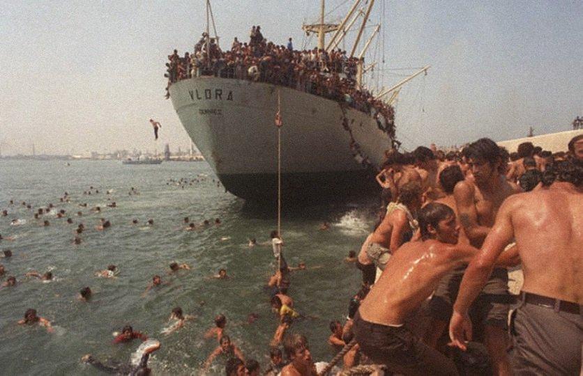 V roce 1991 došlo k prudkému zhoršení hospodářské situace v Albánii. Mimo jiné, byl zaveden přídělový systém. Mnoho lidí v této době emigrovalo do Itálie. Fotografie zachycuje příjezd tisíců albánských uprchlíků , kteří přijíždění do italského Bari.