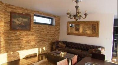 Obývací pokoj jak z klubu pro anglické gentlemany. Netradiční jsou velmi úzká okna.