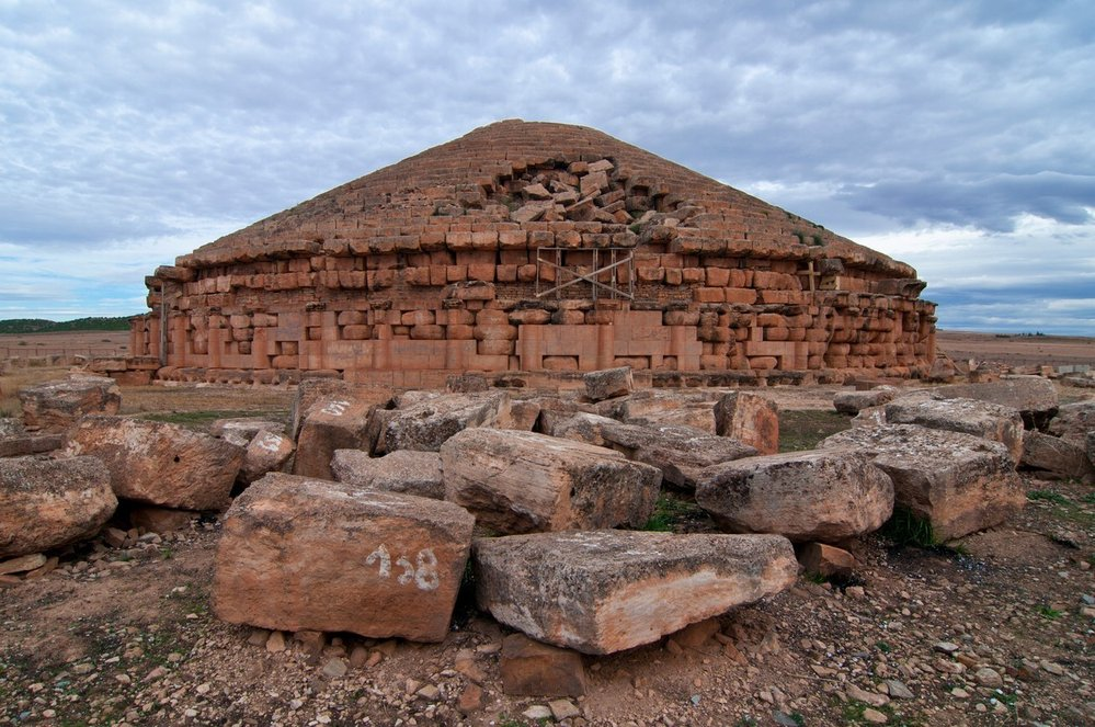 Madghacen (Medracen): Královská hrobka Madghacen na východě Alžírska je typickým příkladem berberské hrobky typu bazina. Tyto hrobky byly v pradávných časech běžně stavěny na okraji pouště. Kamenná konstrukce je nejstarším mauzoleem v Maghrebu – byla postavena pro neznámého krále Numidie ve 4. století př. n. l. Madghacen měří v průměru 59 metrů a je obehnán šedesáti dórskými sloupy, což poukazuje na raný řecký vliv.