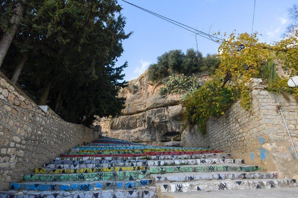 """Schody v Kesře: Berberská vesnice Kesra vklíněná do skal v horách severního Tuniska je jedním z nejstarších berberských osídlení v zemi. Kesra, známá mezi místními jako """"princezna hor"""", láká na dlouhou historii i na romantická zákoutí. Úzké uličky provedou návštěvníky kolem byzantské pevnosti a ukážou na mnohé aspekty života Berberů prostřednictvím dnešních obyvatel i místního muzea. Slavné nabarvené schody pokryté písmeny prastaré berberské abecedy pak vedou až na vrchol srázu k vodním pramenům, které dávají život vesnici a také lánům olivovníků a fíkovníků, které ji obklopují."""