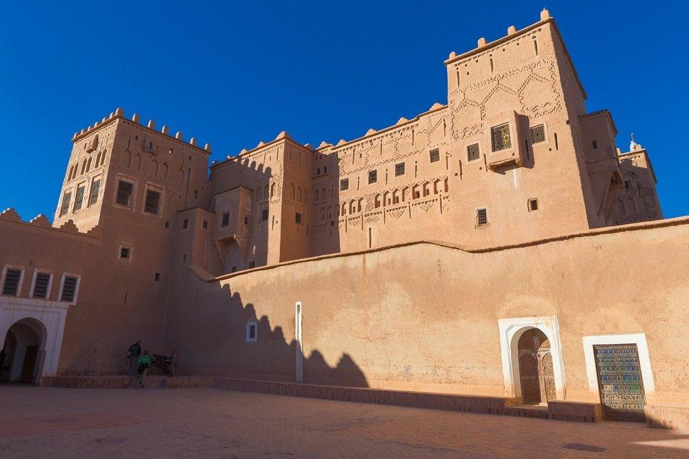 """Warzazát (Ouarzazate): Turistickým centrem jižního centrální Maroka je převážně berberské osídlení Warzazát. Místo známe také jako """"Pouštní brána"""" je pro své historické zázemí oblíbeným cílem filmařů z celého světa. Ve městě stojí několik historických opevněných residencí typu kasba, z nichž nejvýznamnější je kasba Taourirt, která v 19. století patřila významnému rodu Glaoui. Historický charakter města je v ostrém kontrastu s největší solární elektrárnou světa, která se rozléhá ne planině severně od něj."""