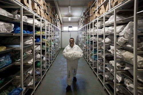 Pracovník mezinárodní skupiny pro chybějící osoby nese vak s lidskými ostatky