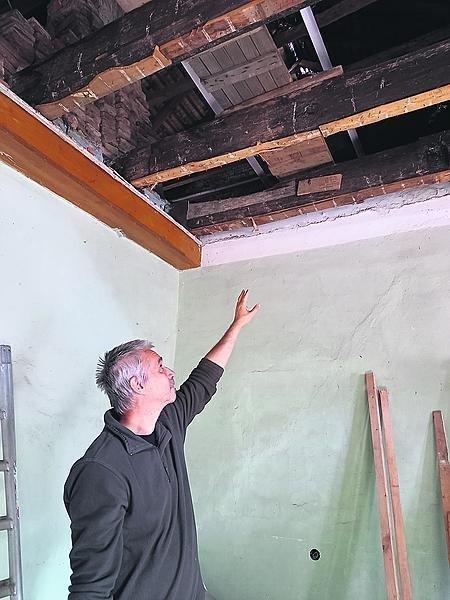 Kastelán ukazuje na dříve trámem skrytou cedulku, připomínku druhé světové války.