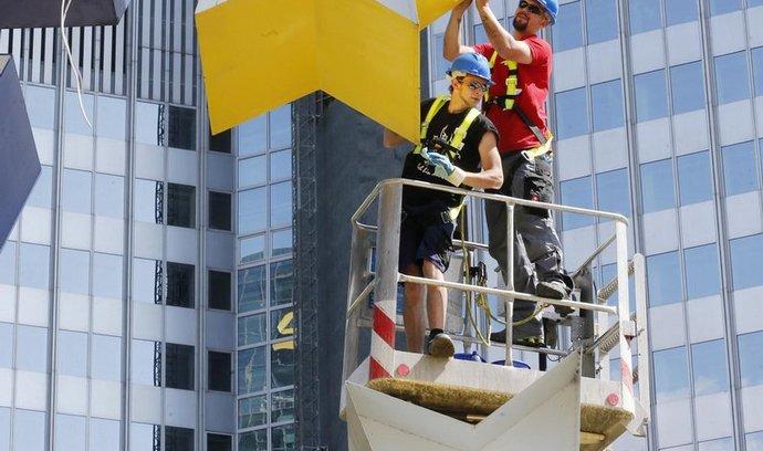 Dělníci čistí hvězdy na logu eura před sídlem ECB
