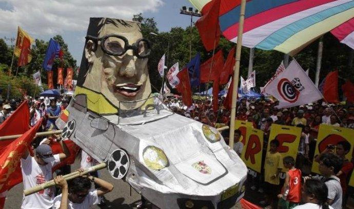 demonstranti na Filipínách s karikaturou prezidenta v jeho luxusním voze