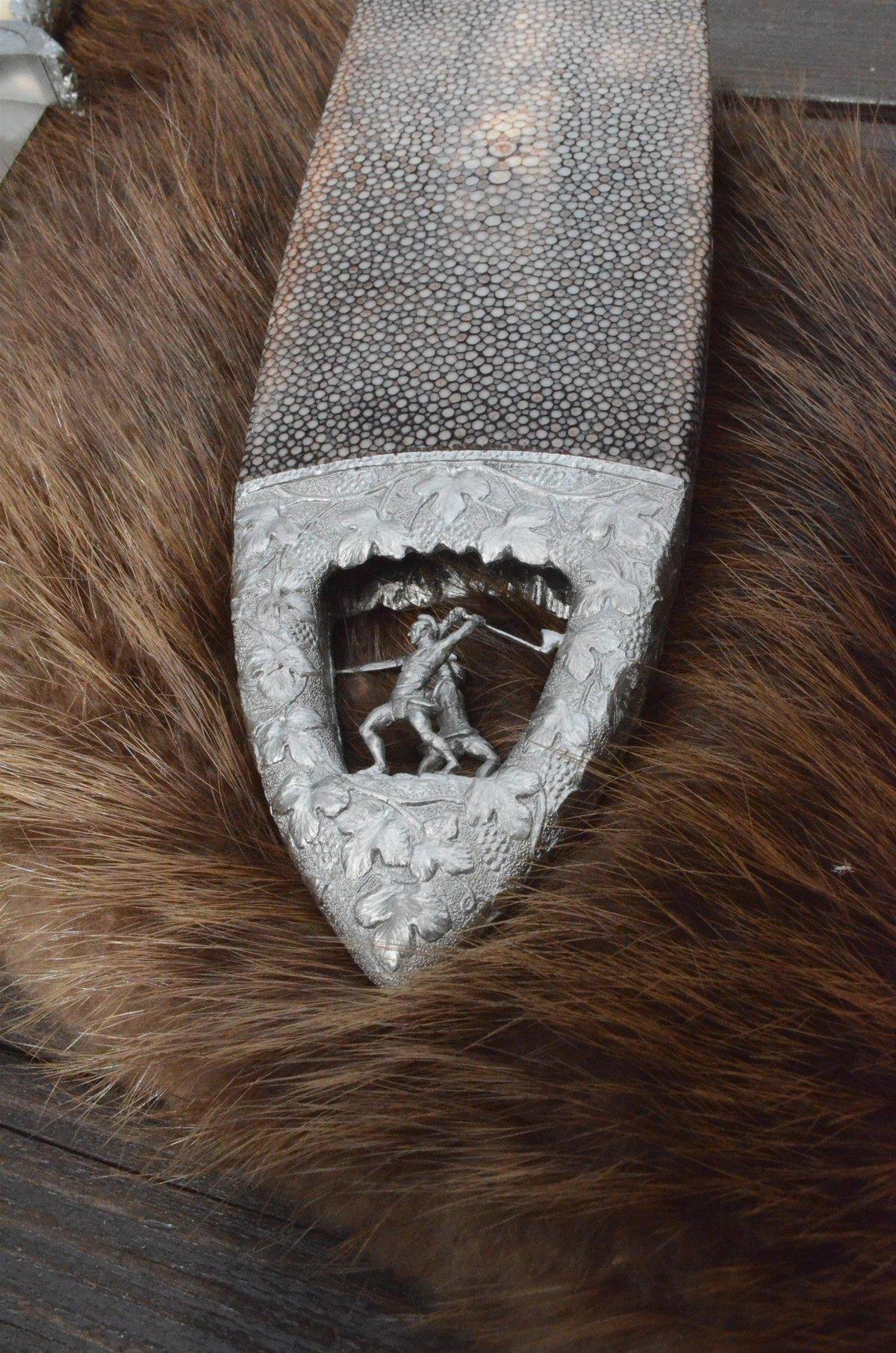 Pouzdro vyrobené z rejnočí kůže je zakončeno detailem souboje dvou gladiátorů.