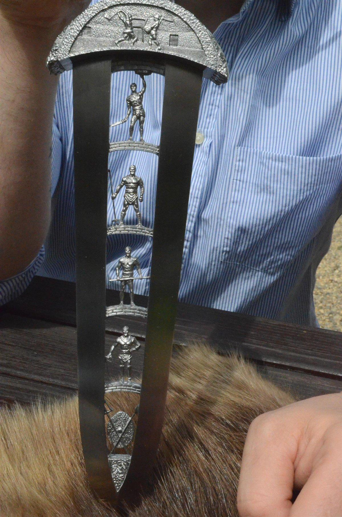 Detail čepele, kde jsou zobrazeni gladiátoři s tradičními zbraněmi.