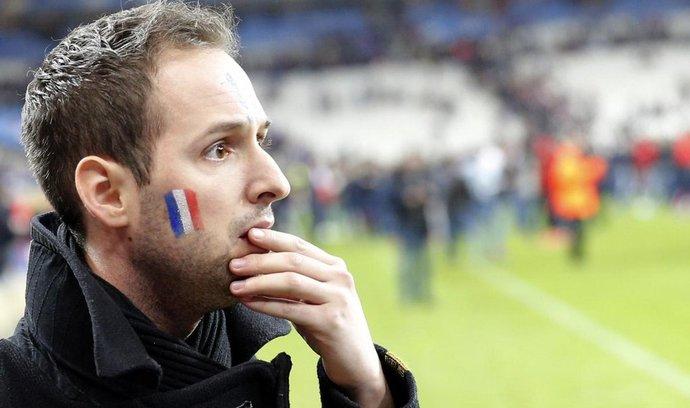 Fotbalový fanoušek na stadionu Stade de France reaguje na zprávu o teroristických útocích
