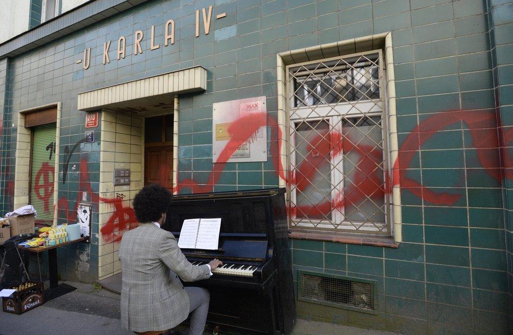 Teplický radní Dominik Feri hraje na klavír před posprejovaným Café V lese.