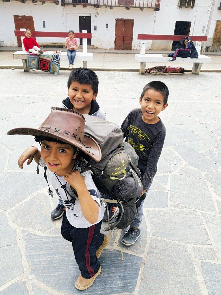Kluci v peruánské vesničce mi právě zabavili batoh, aby si vyzkoušeli, jak je těžký. A s ním i klobouk.