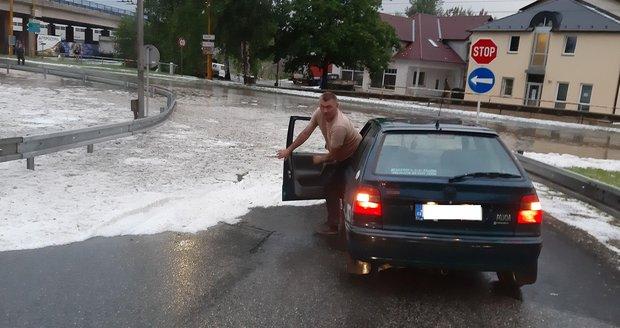 Tento řidič se do centra města nedostal, po sjezdu z dálničního přivaděče uvízl v téměř půl metru hluboké laguně krup a tekoucí vody.