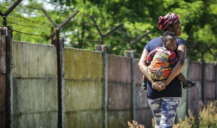 Migrantka se svým dítětem u zdi uprchlického tábora v maďarském Debrecíně