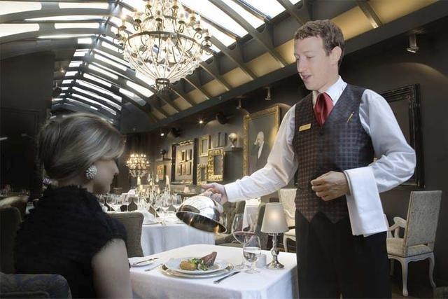Zakladatel Facebooku Mark Zuckerberg jako číšník; má jmění v hodnotě 33.7 miliard $