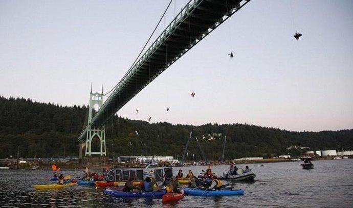most, z něhož aktivisté Greenpeace blokují průjezd lodí