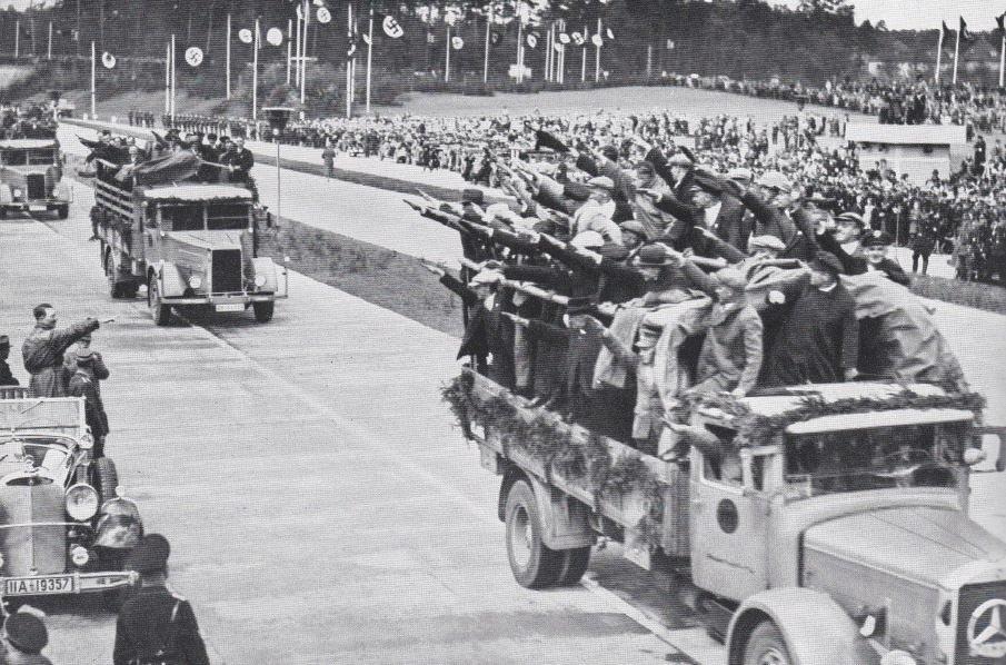 V Německu se stavěly ve velkém dálnice. Hitler (stojí vlevo v autě) zdraví dělníky na jednom z dokončených úseků. Masa také nadšeně hajluje