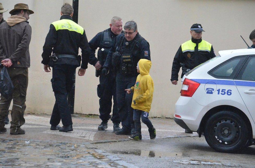 Jednoho z výtržníků odvádějí policisté.