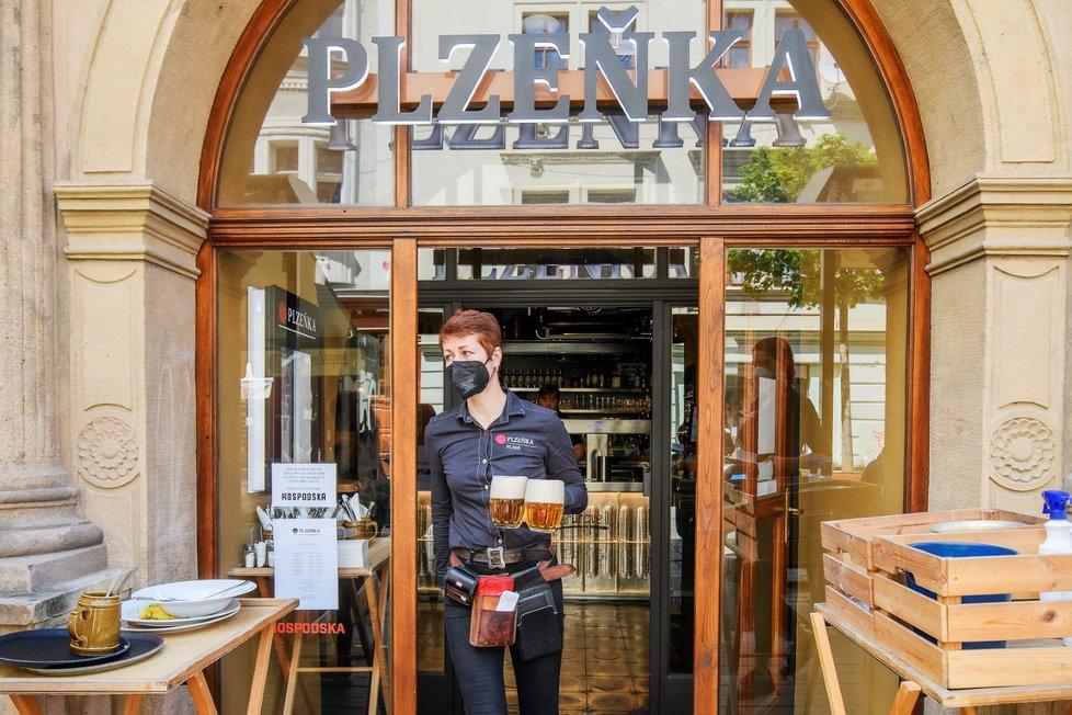 Servírka nese půllitry s pivem hostům na zahrádce plzeňské restaurace Plzeňka, která po rozvolnění protiepidemických opatření otevřela také vnitřní prostory (31. 5. 2021)