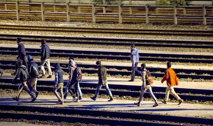 Po kolejích. Parta migrantů se ve francouzském Calais chystá dostat do Anglie po kolejích tunelu pod Lamanšským průlivem