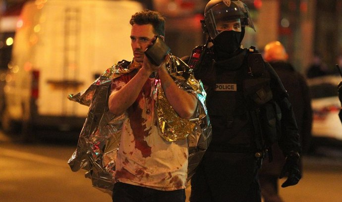 Policista vyvádí zraněného z koncertní síně Bataclan