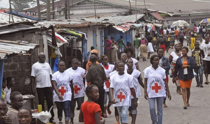 pracovníci Červeného kříže prochází jedním z táborů v karanténě v liberijské Monrovii