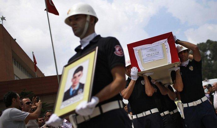 Příslušník tureckých ozbrojených složek s portrétem zemřelého