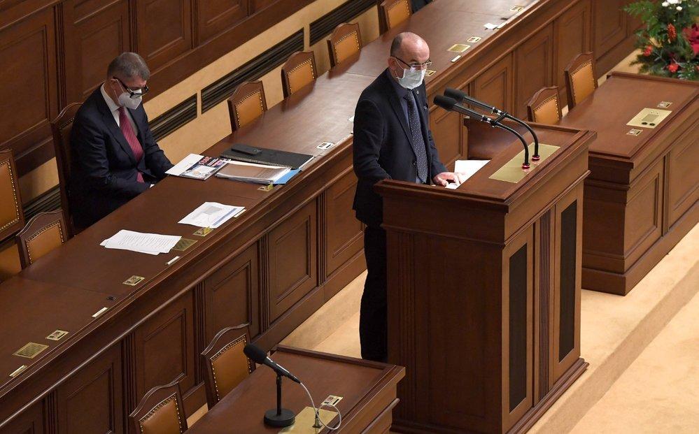 Ministr zdravotnictví Jan Blatný (za ANO) hovoří na mimořádné schůzi Poslanecké sněmovny. Vlevo sedí premiér Andrej Babiš (ANO) (9. 12. 2020)