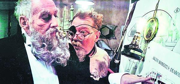 Šílený vědec Orfanik a hrabě Gorc. U rýsovacího prkna stojí za povšimnutí petrolejka, ze které ale ční žárovka.