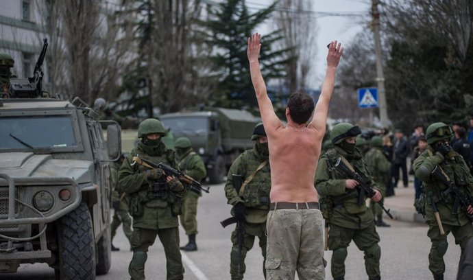 Ukrajinský muž stojí před vojáky ruské armády na předměstí Sevastopolu