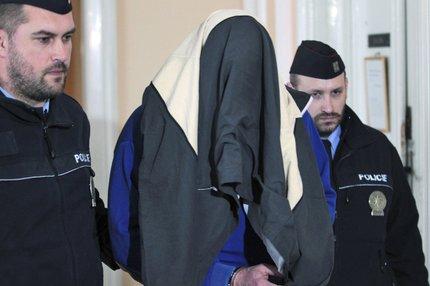 Policisté převezli obviněného do vazby. Tvář skrýval.