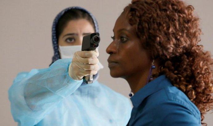 Zdravotnice měří teplotu jedné z cestujících na letišti v Casablance