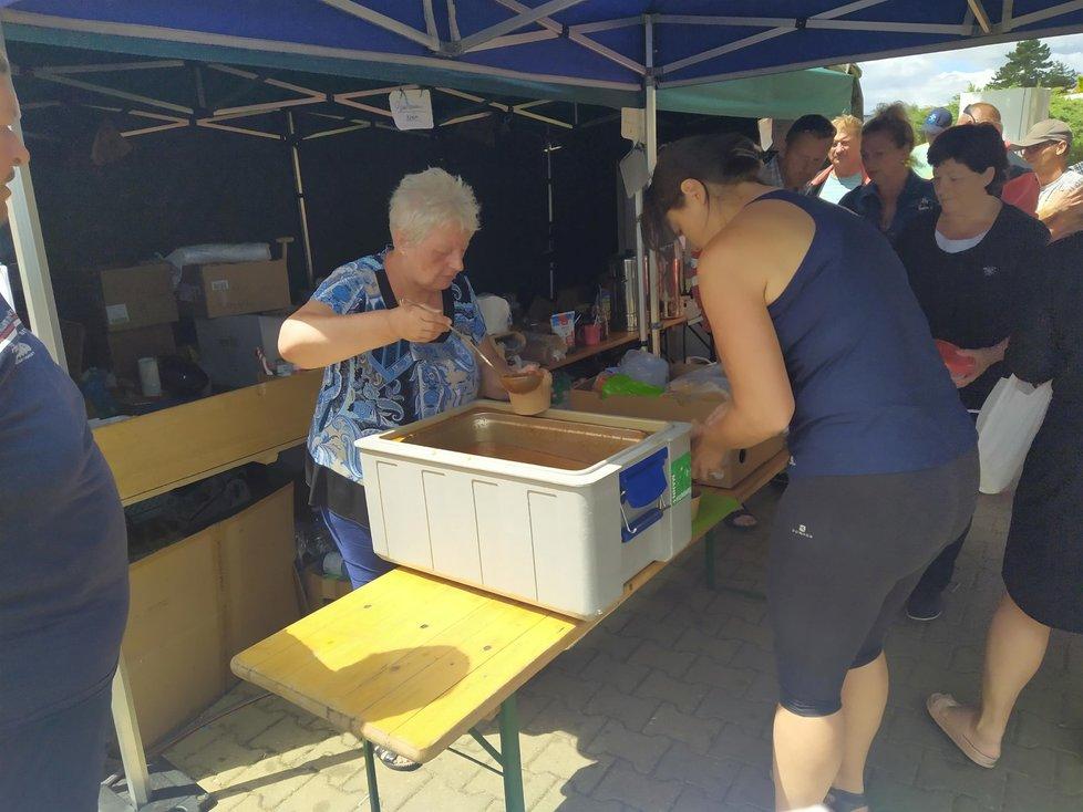 Paní z Hrušek vydává oběd brigádníkům, kteří přijeli do vsi pomáhat po tornádu (3. 7. 2021)