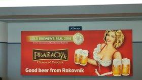 Vyprsená Pražačka s pivem v ruce vítá turisty: Kontroverzní reklama na letišti v Praze dál zůstává