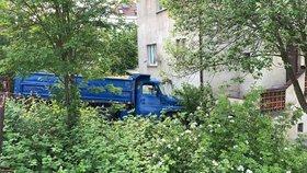 Na co řidič myslel? Tatrovka v Ruzyni probourala plot a napálila to do domu