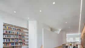V bývalém skladu vznikl minimalistický loft se skrytou ložnicí a obří knihovnou